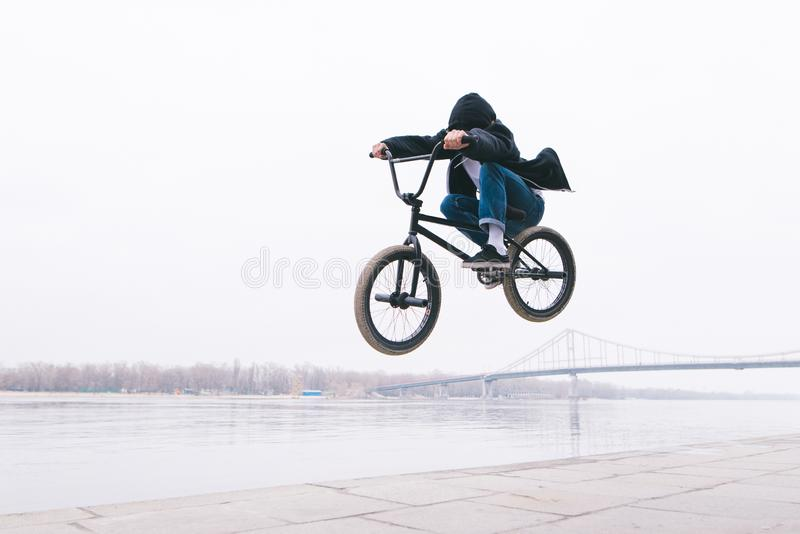 BMX自由式 小孩在BMX自行车跳 BMX车手在河的背景做把戏 库存图片