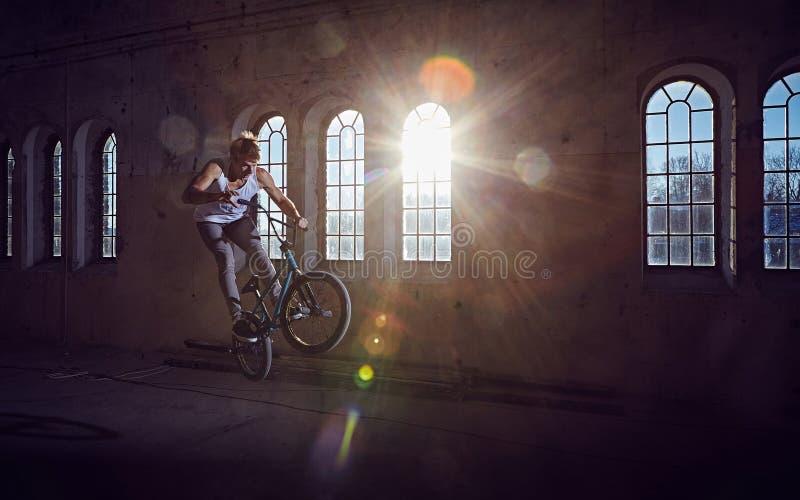 BMX特技和跃迁骑马在有阳光的一个大厅里 免版税图库摄影