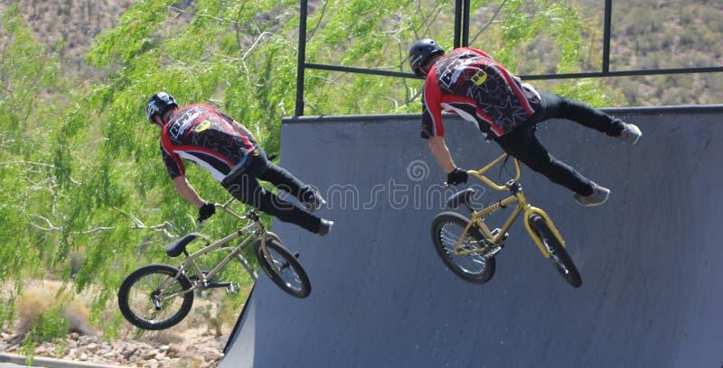 Bmx骑自行车的人一前一后跳 免版税库存照片