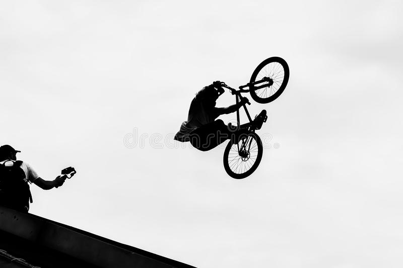 BMX bike jumping in the sky on high speed, black and white silhouette. Extrem Sport stock photo
