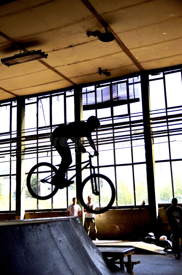 BMX bike riders. Group of young freestyle bike riders during a performance in an industrial unit stock images