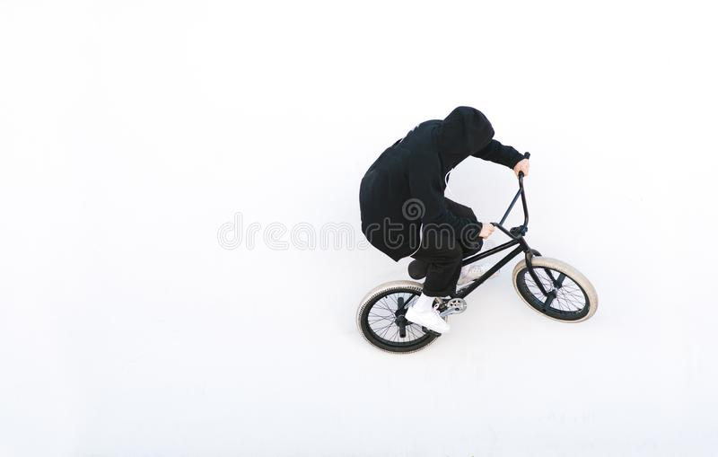 Bmx cyclist in dark clothes rides on a white background. Bike rider on bmx bike isolated on white background stock images