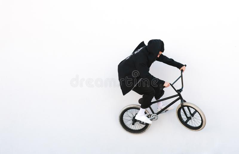Bmx cyclist in dark clothes rides on a white background. Bike rider on bmx bike isolated on white background royalty free stock photography