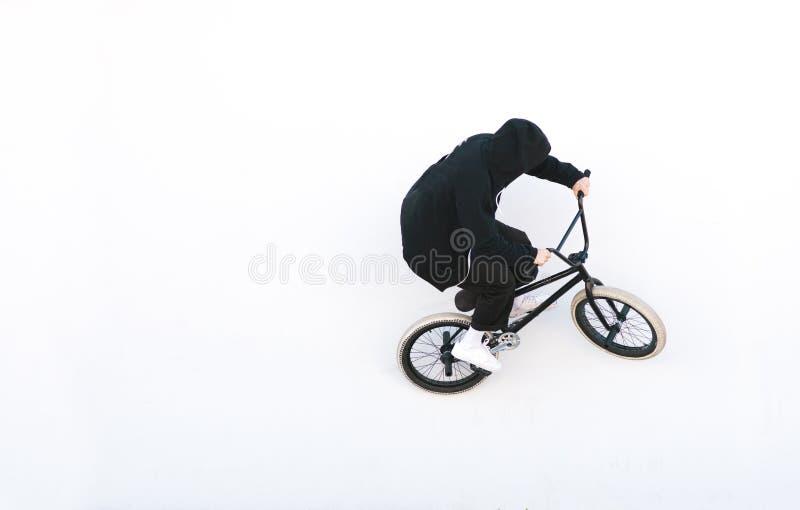 Bmx cyklista w zmroku odziewa przejażdżki na białym tle Roweru jeździec na bmx rowerze odizolowywającym na białym tle obrazy stock
