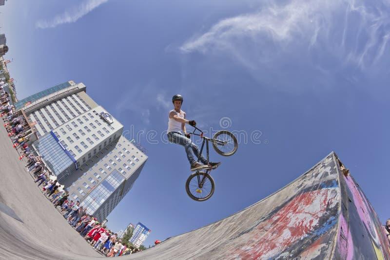 BMX-de fietser voert een stuntsprong uit stock fotografie