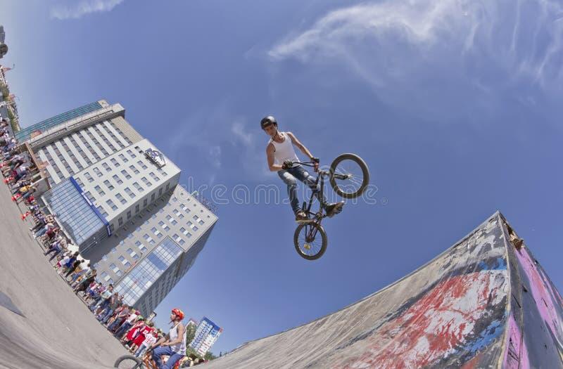 BMX-de fietser voert een stuntsprong uit stock afbeelding