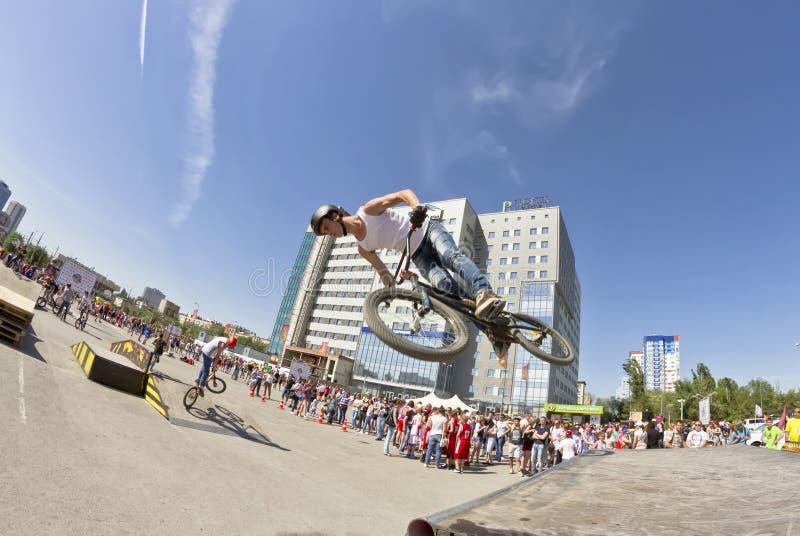 BMX-de fietser voert een stuntsprong uit stock afbeeldingen