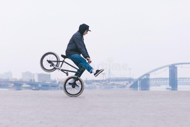 BMX-Fahrradreiterfahrten auf das Vorderrad vor dem hintergrund der minimalistic Stadtlandschaft BMX-Konzept lizenzfreie stockbilder