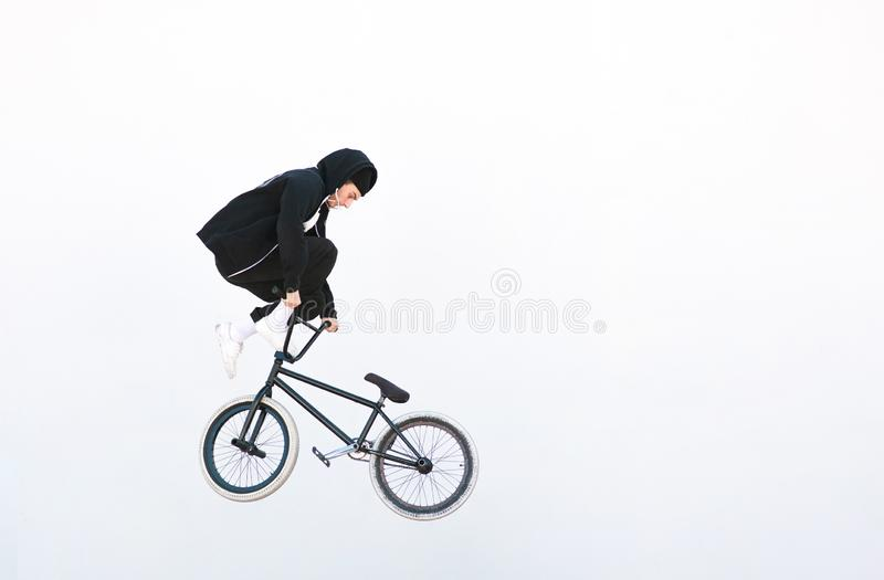 Bmx freestyle on the background of a white wall. BMX rider makes a TAilwhip trick on a white background royalty free stock photography