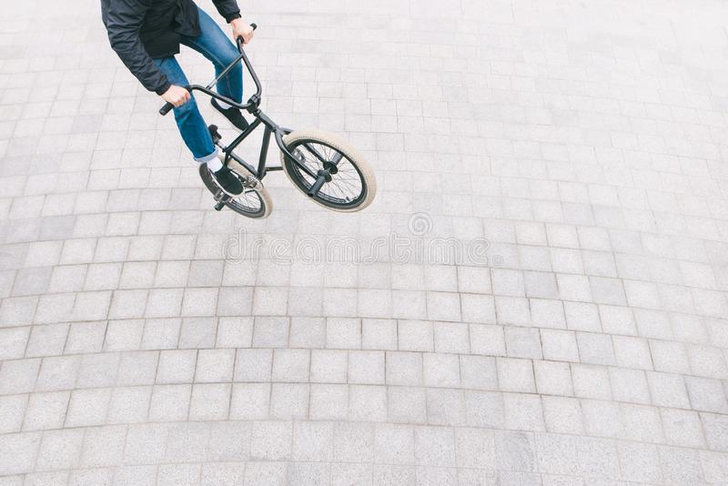 BMX freestyle on the square top view. young man is doing tricks on a BMX bike. BMX culture. BMX freestyle on the square top view. A young man is doing tricks on royalty free stock image