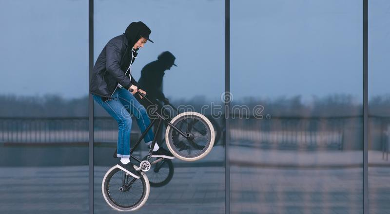 BMX freestyle. man doing tricks on BMX against a dark shop window. Street culture royalty free stock photos