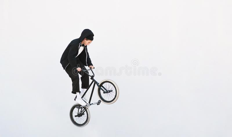 BMX freestyle. Young BMX bicycle makes tricks on the white background. Copyspace royalty free stock image