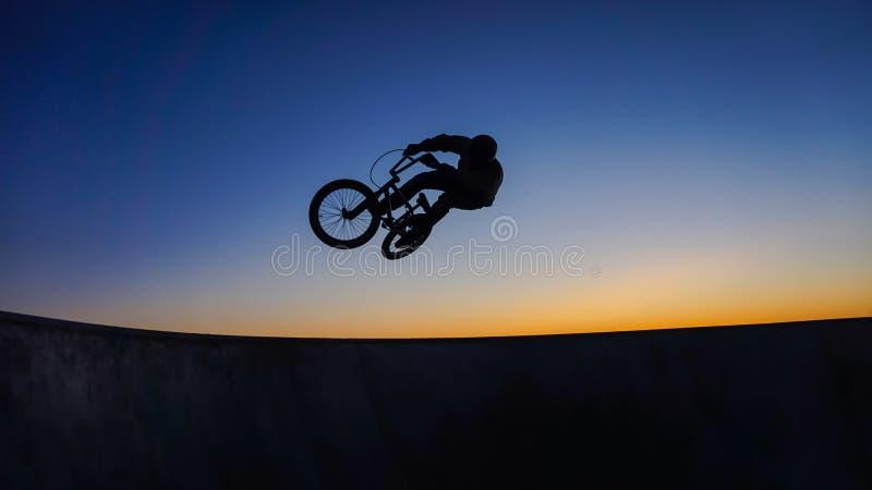 Bmx hoppar konturn mot solnedgång på Portugal arkivfoto