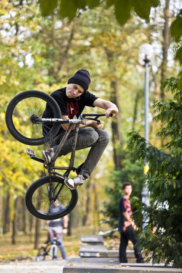 BMX Invert. BMX rider performing air trick invert against a blured bokeh background royalty free stock photography