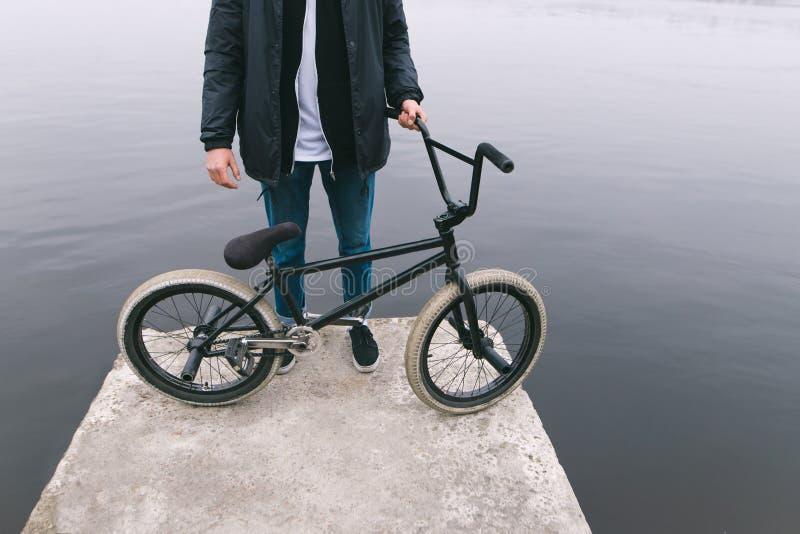 BMX jeźdza stojaki na wodnym roweru molu Bicykl i nogi na tle rzeka Spacer na rowerze fotografia stock