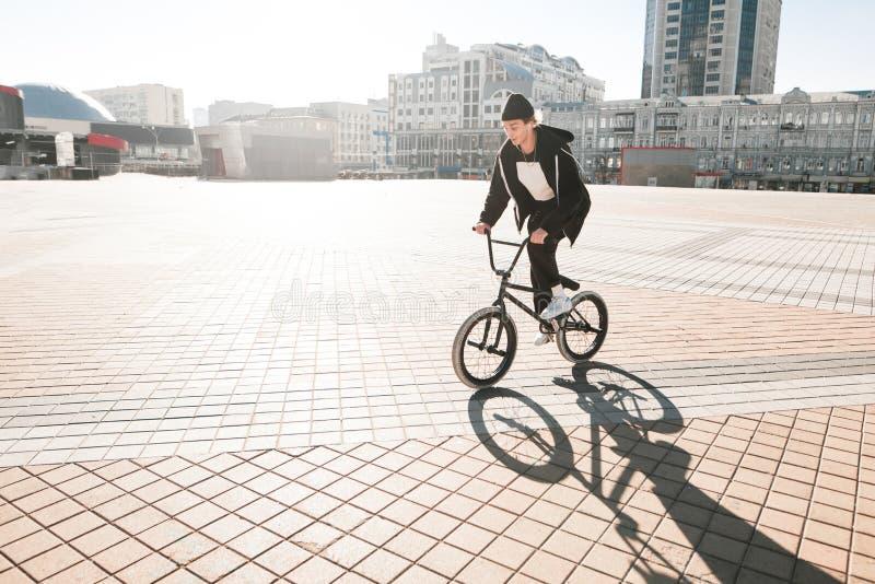 BMX-Radfahrer reiten ein Fahrrad auf das Quadrat an einem sonnigen Tag Junges Reiter bmx Fahrrad geht durch die Stadt lizenzfreie stockbilder