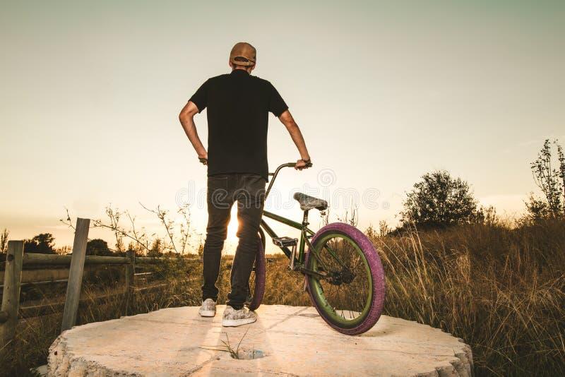 BMX-Reiter bei Sonnenuntergang Kerl, der ein bmx Fahrrad reitet lizenzfreie stockfotos