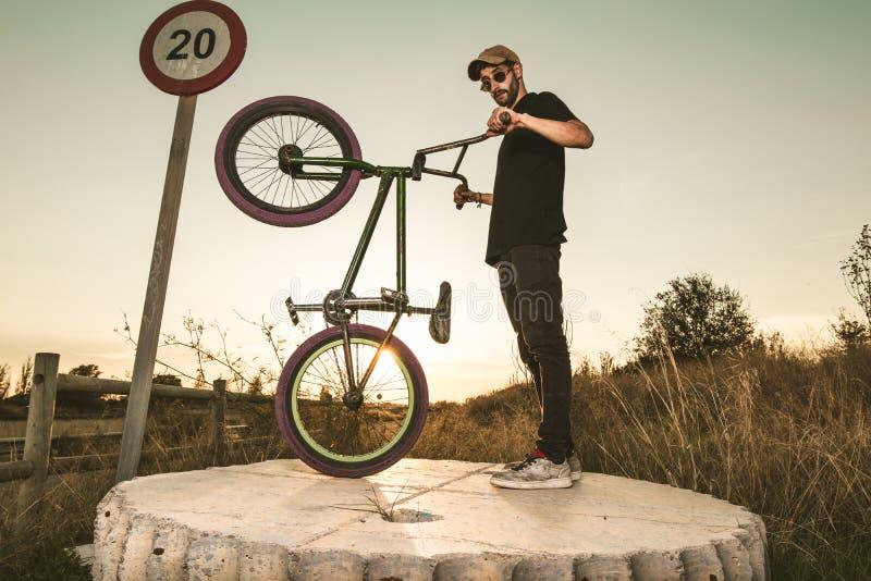 BMX-Reiter bei Sonnenuntergang Kerl, der ein bmx Fahrrad reitet lizenzfreie stockbilder