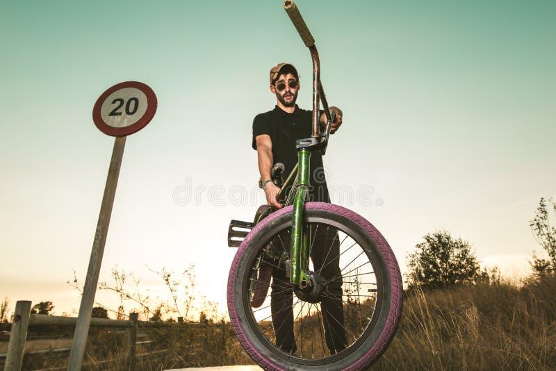 BMX-Reiter bei Sonnenuntergang Kerl, der ein bmx Fahrrad reitet stockfotografie