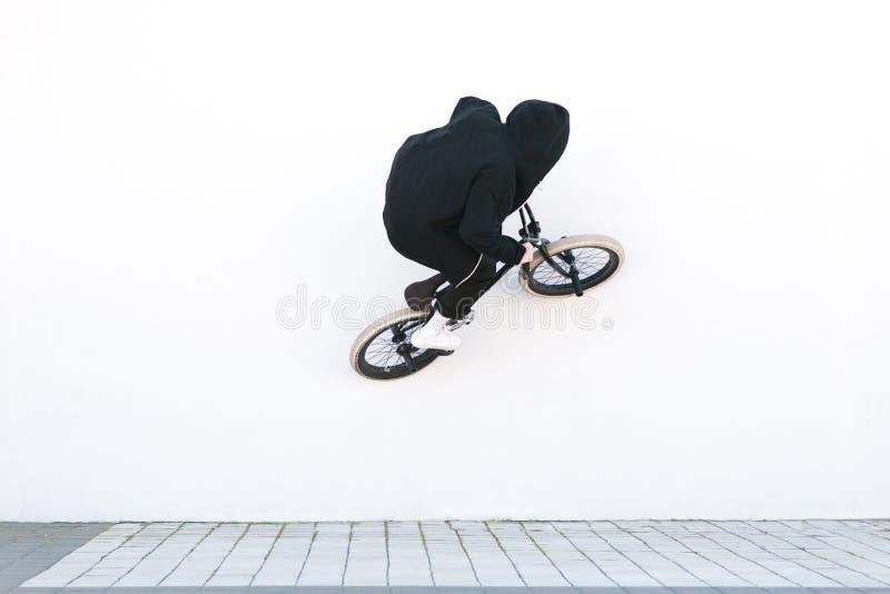 BMX-Reiter fährt Fahrrad auf die weiße Wand Junger Mann tut Tricks auf BMX stockfotografie