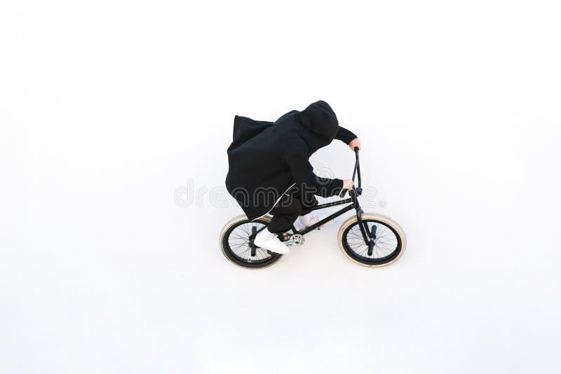 BMX-Reiter fährt Fahrrad auf die weiße Wand Junger Mann tut Tricks auf BMX stockbild