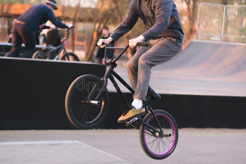 Bmx-Reiter macht Tricks auf BMX in einem Skateboard Glättung des Trainings bei Bmx Ein Radfahrer reist auf das Hinterrad BMX-Konz lizenzfreies stockbild