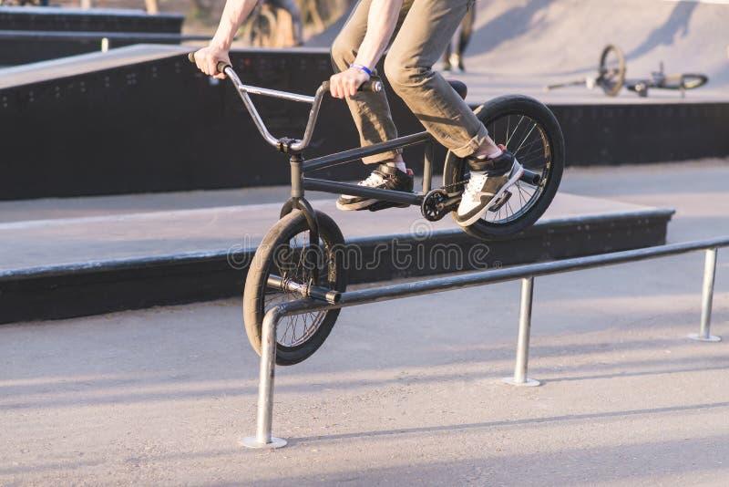 Bmx-Reiterdias entlang den Schienen auf dem Vorderrad Das jugendlich tut Tricks auf einem bmx Fahrrad BMX-Konzept lizenzfreies stockbild
