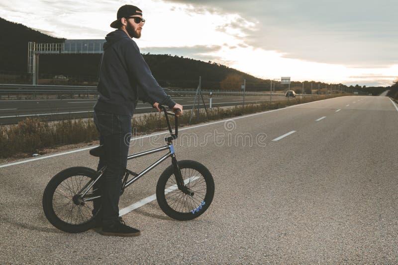 BMX Rider Doing Tricks Homem novo com uma bicicleta do bmx Esportes extremos imagens de stock royalty free