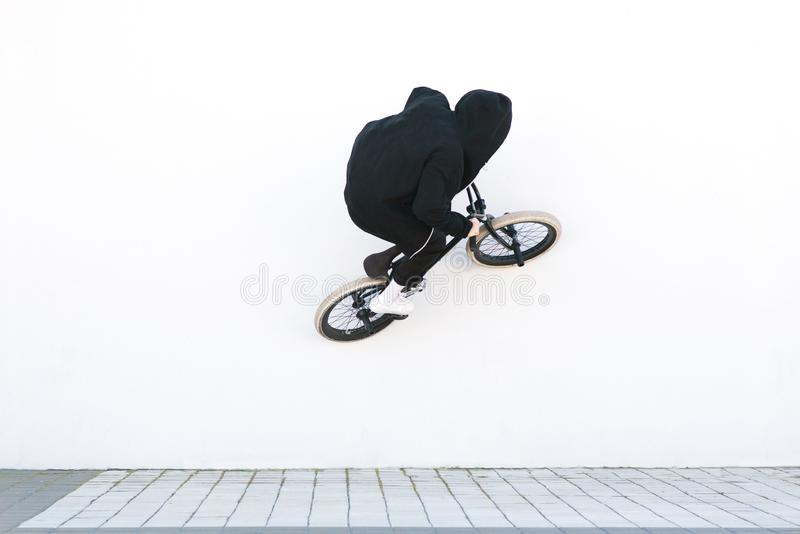 BMX rider rides a bicycle on the white wall. Young man is doing tricks on BMX stock photography