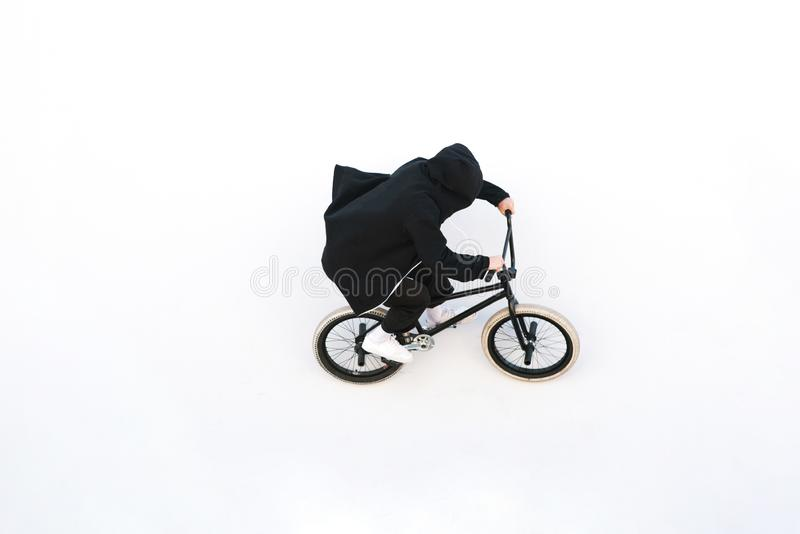 BMX rider rides a bicycle on the white wall. Young man is doing tricks on BMX stock image