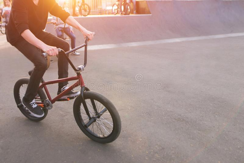 Bmx rider rides a skate park in the background of the sunset. Evening training at Bmx royalty free stock images