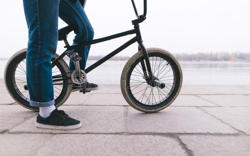 BMX rider stands with a bike in the outdoors. BMX concept. Street style royalty free stock photography