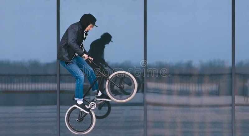 BMX styl wolny mężczyzna robi sztuczkom na BMX przeciw zmroku sklepu okno Uliczna kultura zdjęcia royalty free