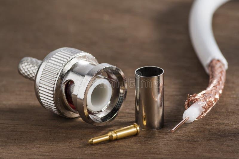 BNC włącznik dla przesyłowego szybkozmiennego sygnału i kawałek ochroniony kabel na drewnianym tle obrazy stock