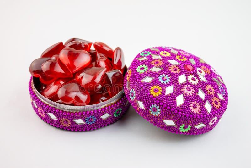 Boîte à bijoux colorée complètement de coeurs rouges sur le bacground blanc - concept de Saint Valentin photo stock