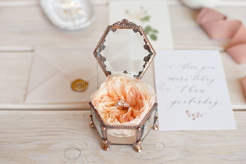 Bo?te ? bijoux en gros plan de mariage de cru pour des anneaux de mariage sur un fond en bois avec une carte de voeux et des fleu images stock