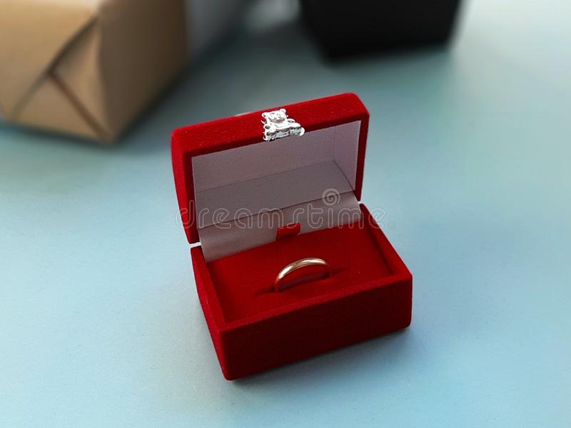 Boîte à bijoux rouge de velours avec l'anneau d'or sur le fond bleu images stock