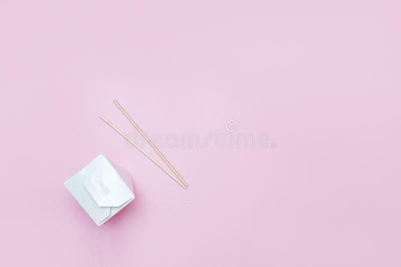 Boîte à emporter ouverte pour les nouilles chinoises présentées avec des baguettes, sur le copyspace flatlay d'ensemble au détail images stock