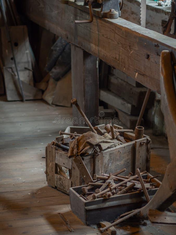 Boîte à outils antique se reposant sur le plancher d'un atelier rustique photo stock