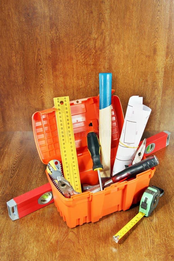 Boîte à outils avec de divers outils de travail sur une table en bois image stock