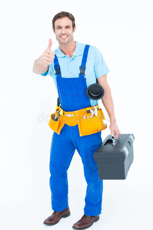 Boîte à outils de transport de plombier tout en faisant des gestes des pouces  photo stock