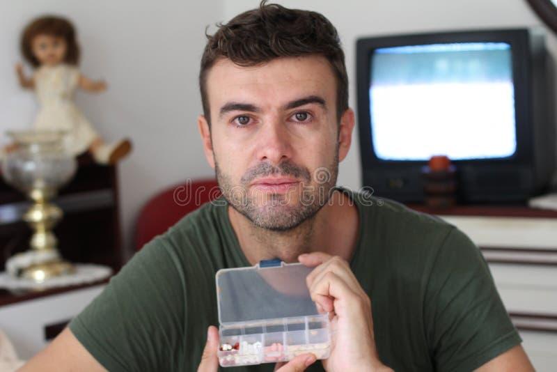 Boîte à pilules de regard malsaine de participation d'homme photo libre de droits