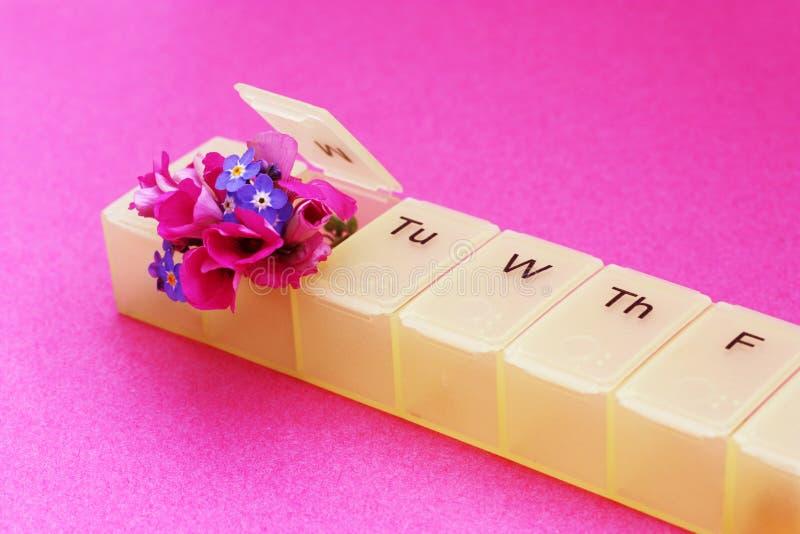 boîte à pilules et fleurs images libres de droits