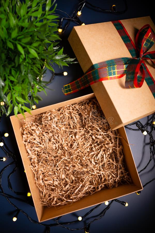 Boîte actuelle de carton ouvert avec le ruban sur le fond bleu entouré par les lumières décoratives photographie stock libre de droits