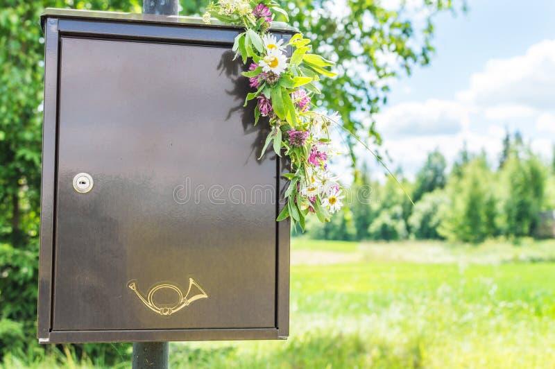 Boîte aux lettres avec la guirlande des fleurs là-dessus images libres de droits