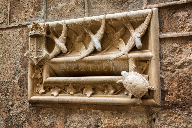 Boîte aux lettres de pierre de style d'Art nouveau décorée des hirondelles et des figurines de tortue sur le mur de la maison de  image stock