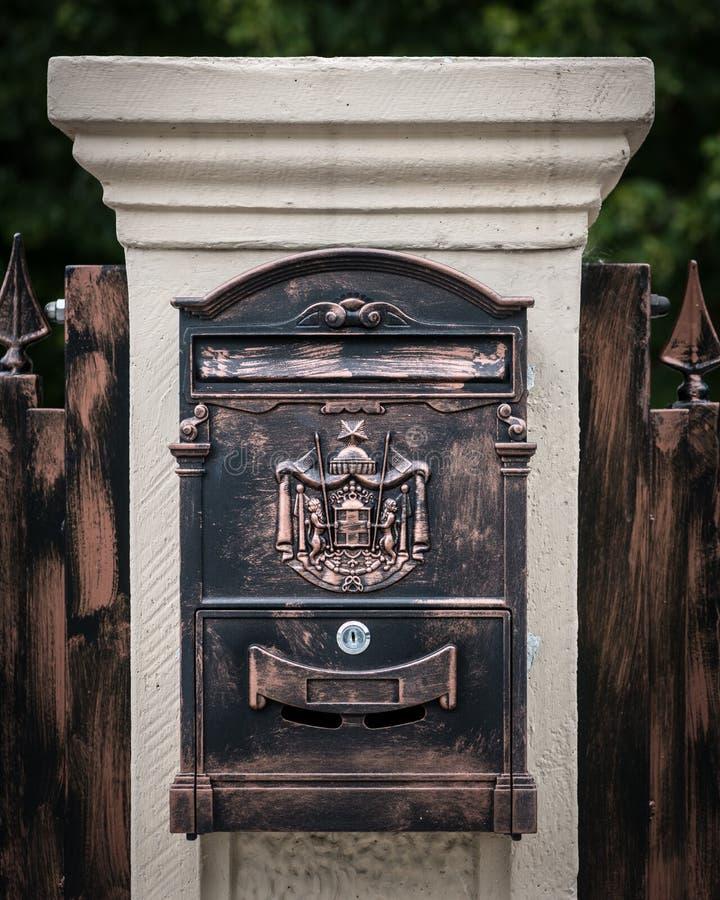 Boîte aux lettres en bronze sur un pilier blanc fait en pierre photographie stock