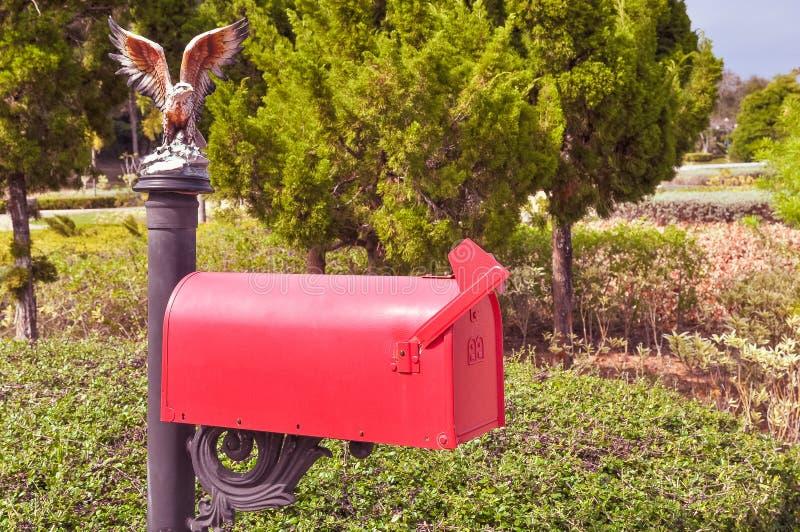Boîte aux lettres rouge anglaise classique sur le pilier photographie stock