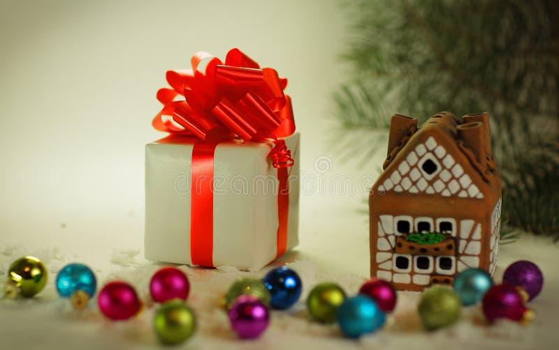 Boîte avec la maison de cadeau de Noël et de pain d'épice sur un Ba de fête photos libres de droits