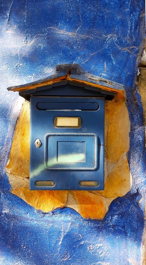 Boîte bleue de courrier sur un mur bleu endommagé photo libre de droits